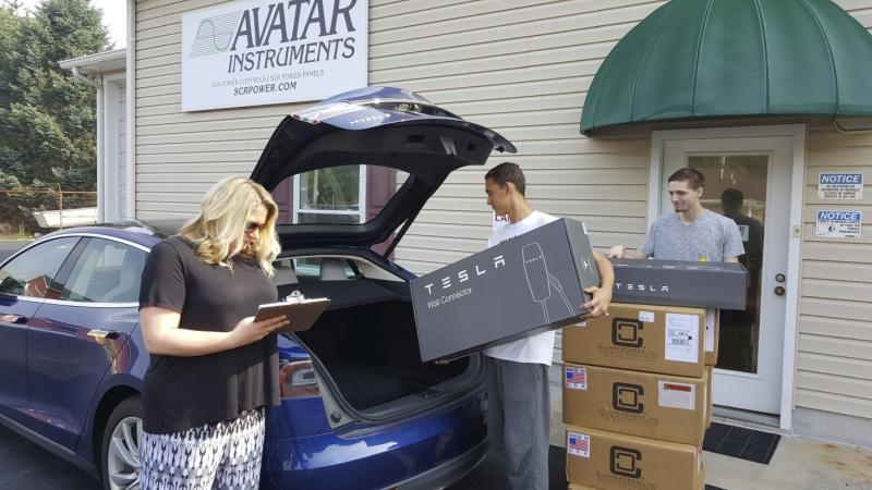 Avatar Instruments Office Manager Stephanie Long Oversees Jacob Crenshaw And Vince Borgesi Loading The Electric Vehicle Charging Station Hardware Into A